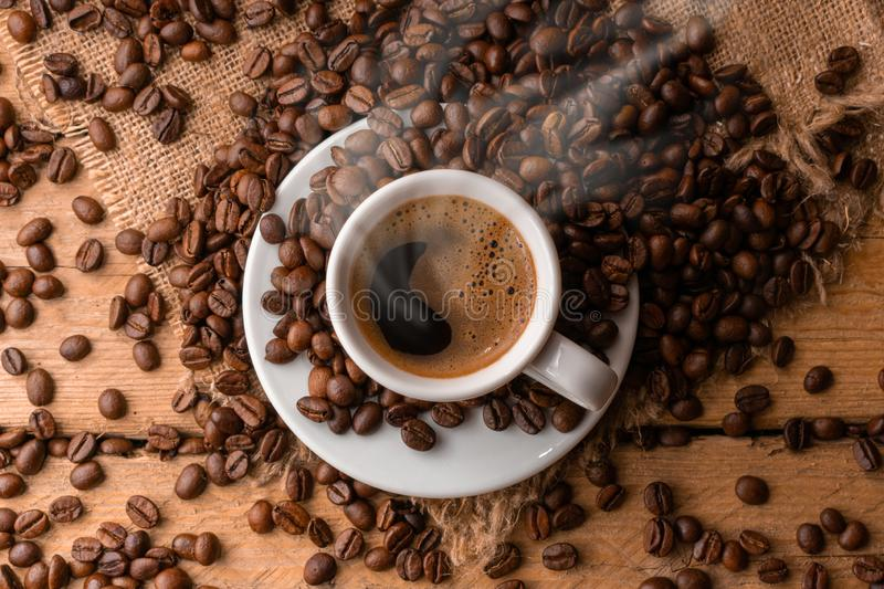 A cup of fresh coffee on burlap. A scattering of coffee beans with a cup of coffee. Coarse fabric stock images