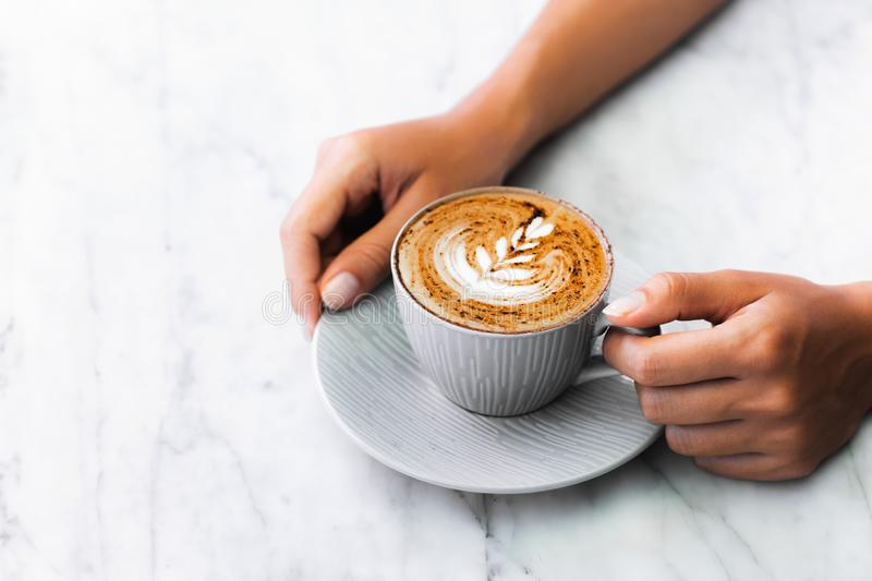 Cup of fresh coffee cappuccino in woman hands. On white marble table trendy background. Classic latte art and chocolate on foam. Empty place for text, copy stock image