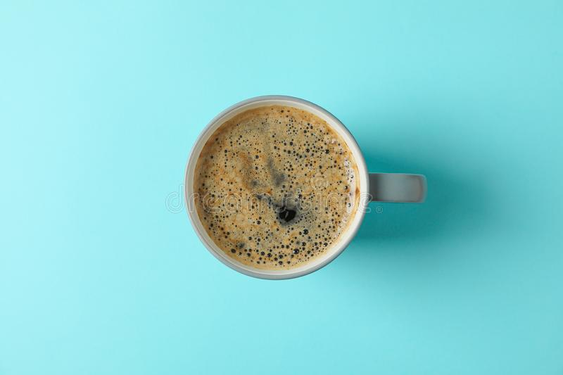 Cup of fresh coffee on color background, space for text. And top view royalty free stock image