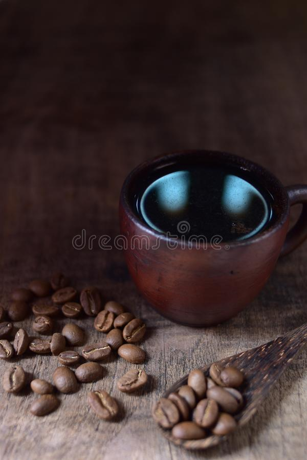 A cup of fresh coffee on old kitchen table. A scattering of coffee beans with a cup of coffee stock image