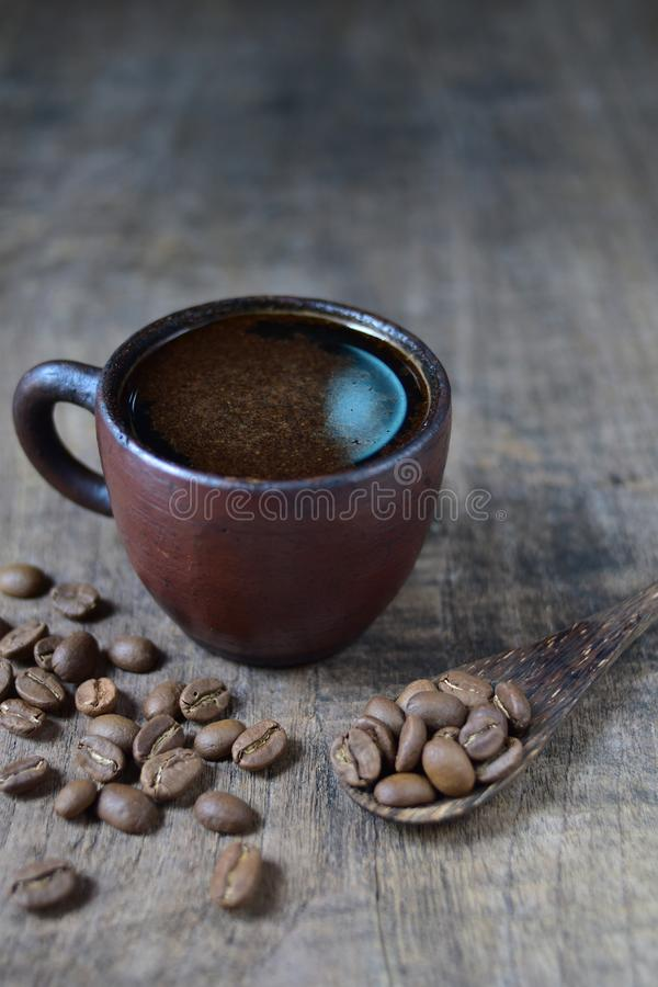 A cup of fresh coffee on old kitchen table. A scattering of coffee beans with a cup of coffee royalty free stock photo
