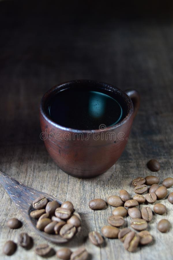 A cup of fresh coffee on old kitchen table. A scattering of coffee beans with a cup of coffee stock photography