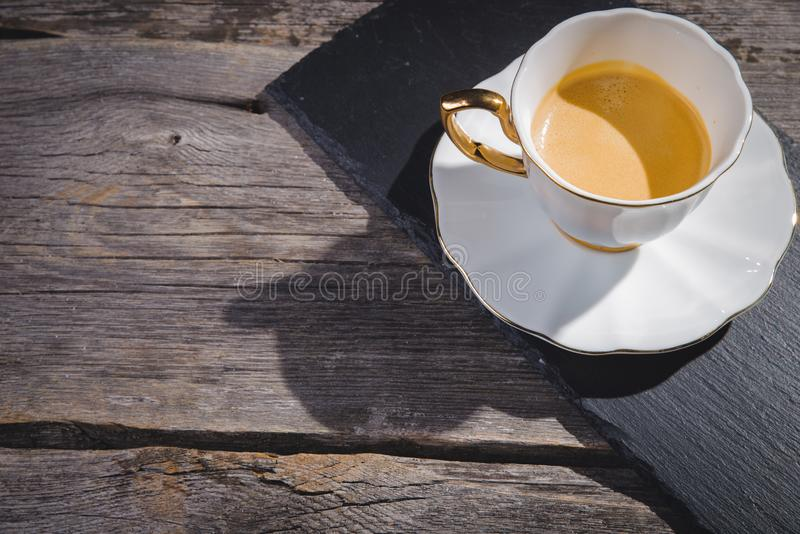 Cup of fresh espresso and roasted coffee beans on dark wooden background stock image
