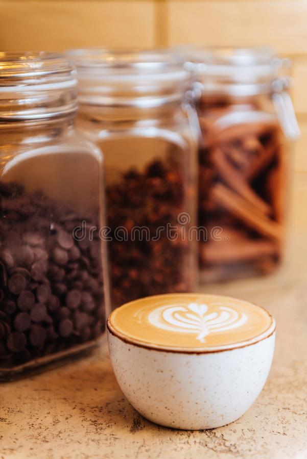 Cup of fresh hot cappuccino with cinnamon sticks royalty free stock photo
