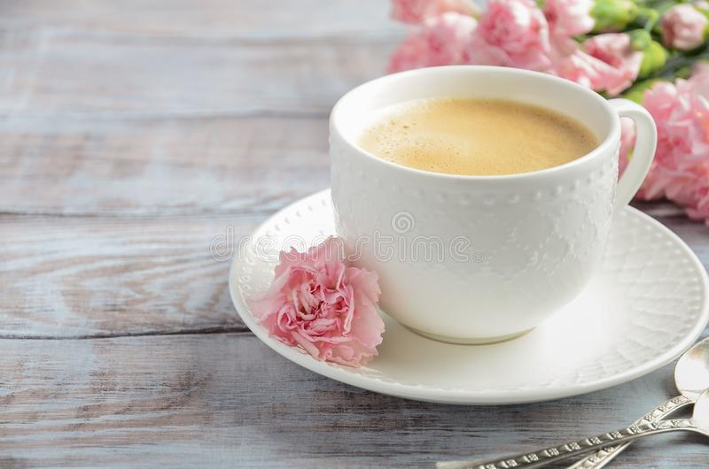 Cup of fresh morning coffee with pink carnation flowers on a wooden background. Valentine`s day concept. stock images
