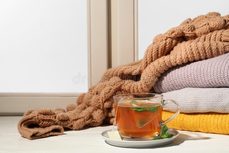 Cup of fresh tea on windowsill, space for text. Winter drink. Cup of fresh tea on windowsill indoors, space for text. Winter drink royalty free stock image