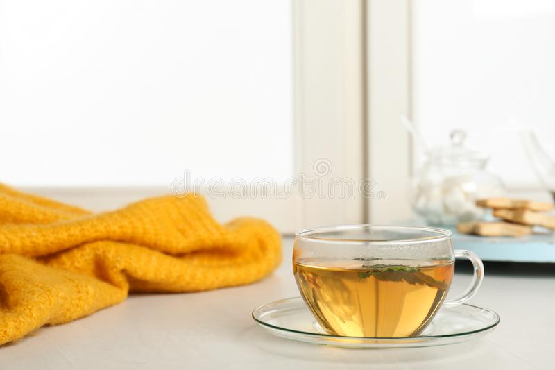 Cup of fresh tea on windowsill indoors. Winter drink. Cup of fresh tea on windowsill indoors, space for text. Winter drink stock photo