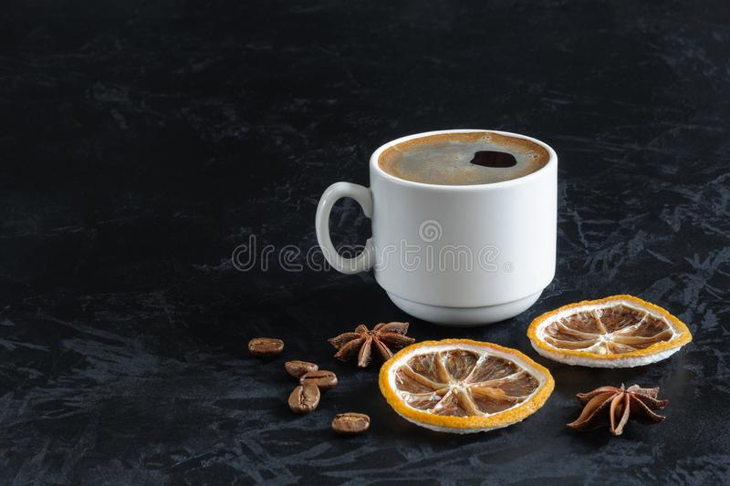 A cup of freshly brewed coffee with froth with dried lemon slices, star anise and coffee beans on a black concrete background. stock images