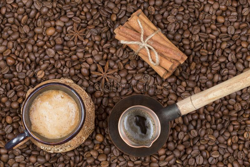 A cup of freshly brewed coffee, pot and cinnamon on coffee beans stock photos