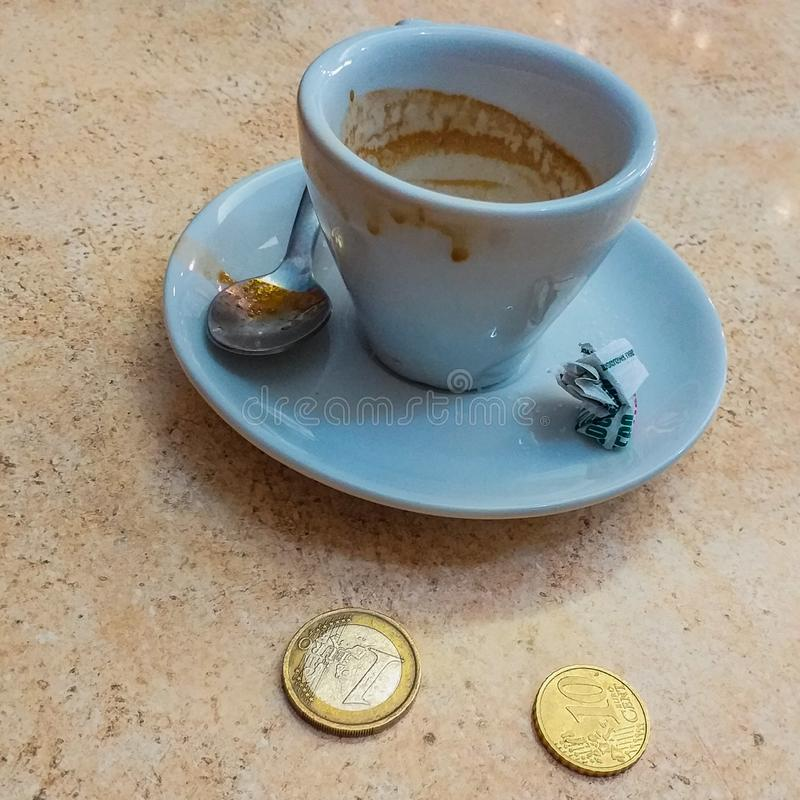 A cup of freshly-drunk espresso with the cost in Italy alongside. coffee is a global busines royalty free stock photo