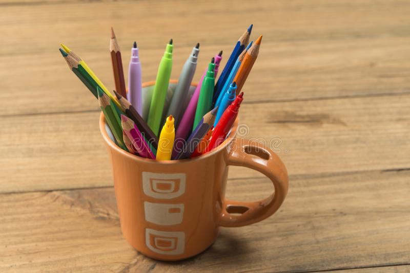 Cup full of markers and colored pencils. Concept of back to school. Cup full of markers and colored pencils stock image