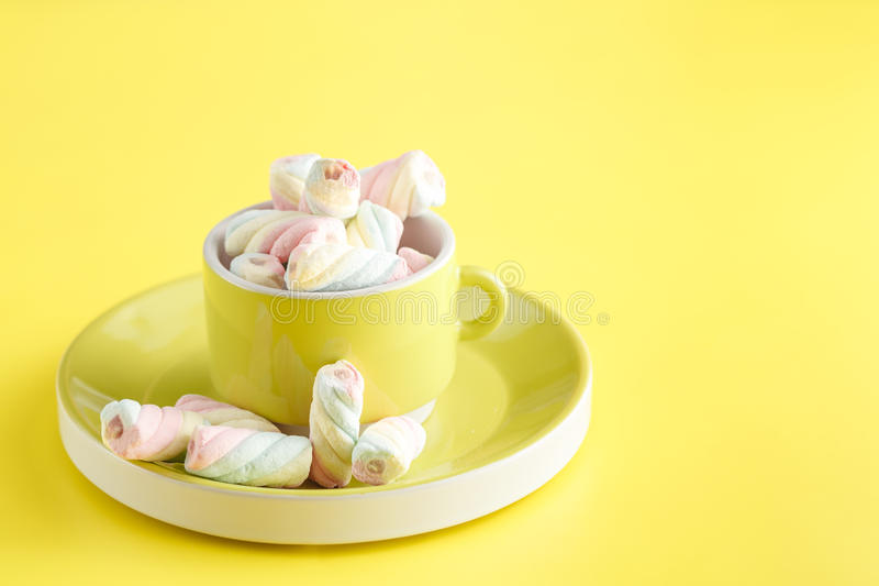Cup full of sweet twisted marshmallow on bright yellow backgrou royalty free stock image