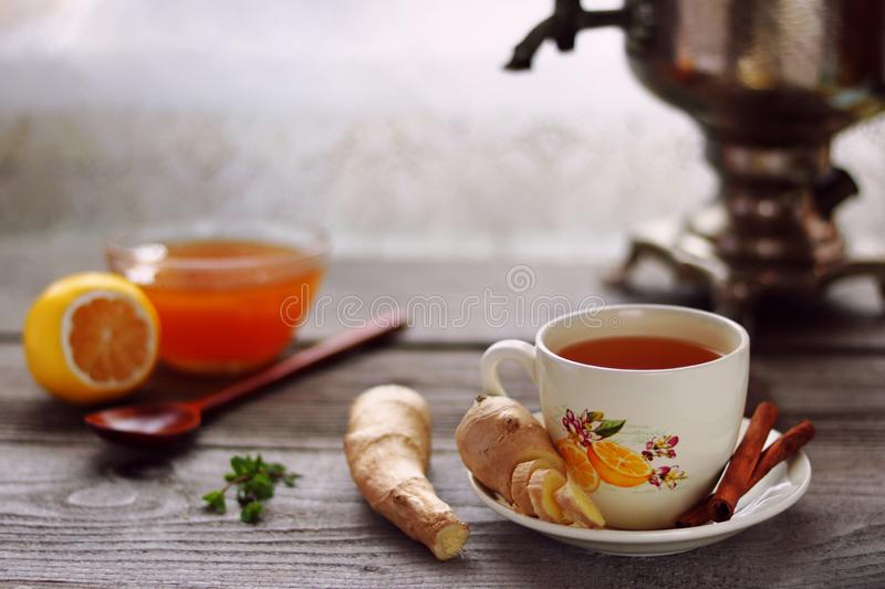 A cup of ginger tea, ginger roots, vintage samovar, lemon and honey royalty free stock photo
