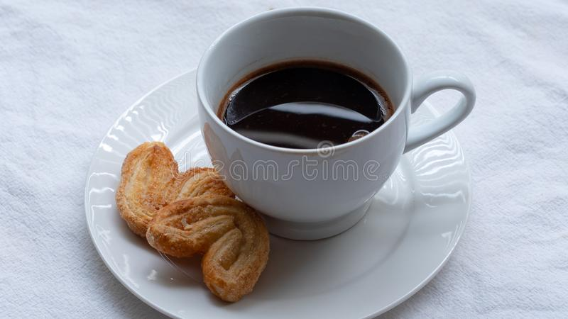 Cup of Greek or Turkish coffee, on small white saucer plate, with two cookie pastries, on white cloth surface stock photos