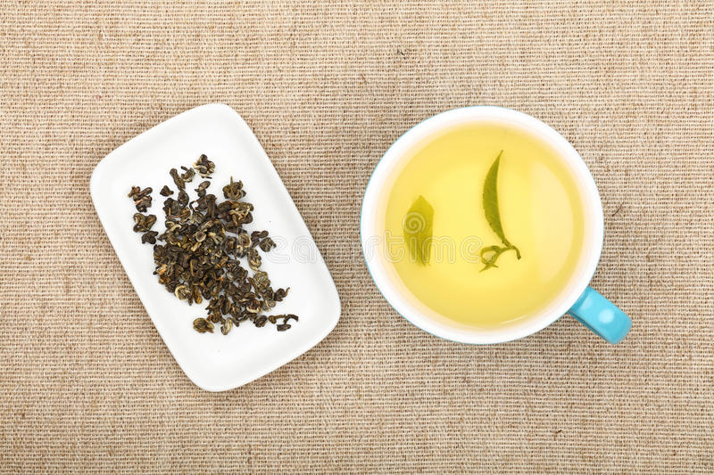 Cup of green tea on canvas tablecloth. Big full cup of green tea and white plate with dried green tea leaves on flax canvas tablecloth, close up, elevated top stock photos