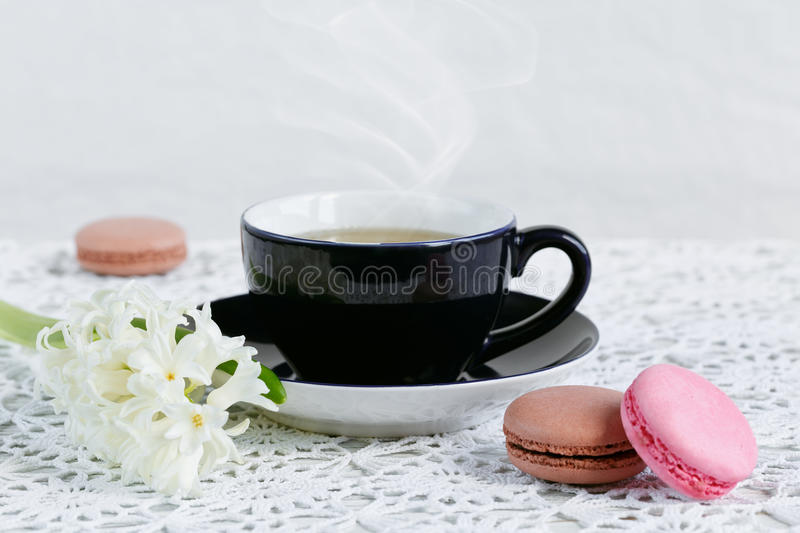 Cup of green tea, color macaroon and white flowers royalty free stock photos