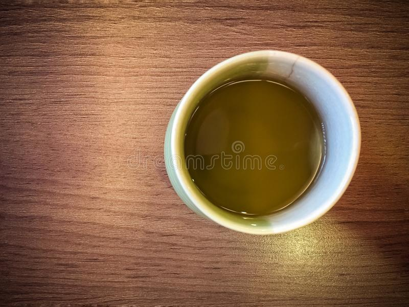 Cup of green tea in Japanese style in wooden table. Cup of green tea in Japanese style. Green tea is made from unfermented leaves and reportedly contains the royalty free stock images