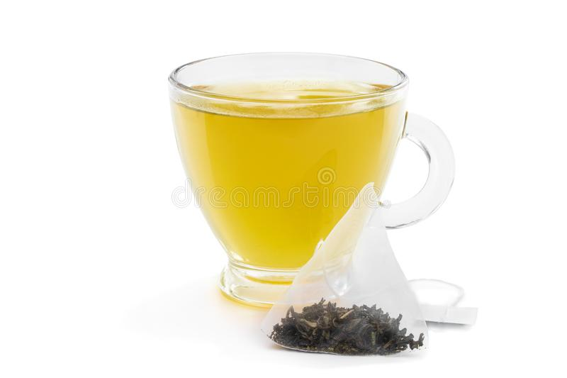 Cup of green tea with jasmine and pyramid tea bag isolated on white. Cup of  green tea with jasmine and pyramid tea bag isolated on white stock image