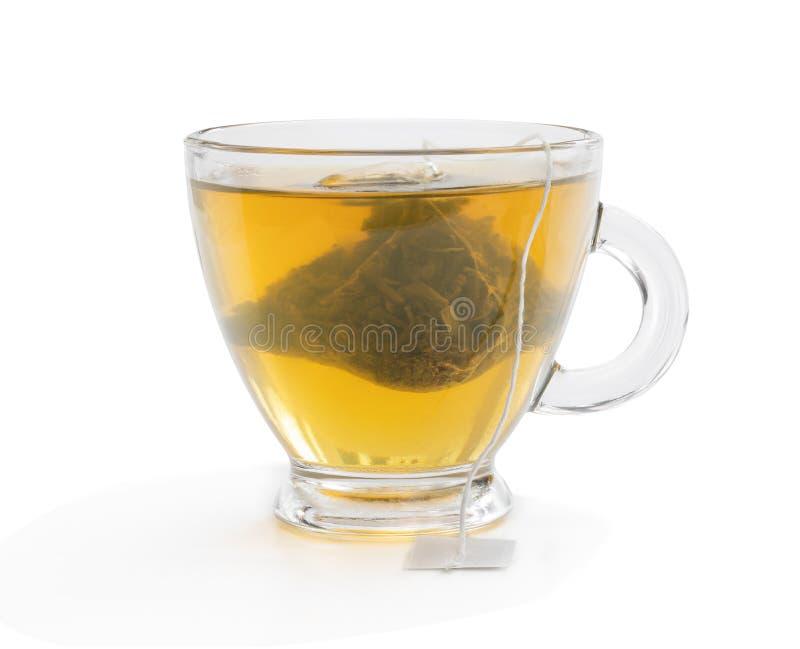 Cup of green tea with jasmine and pyramid tea bag isolated on white. Cup of  green tea with jasmine and pyramid tea bag isolated on white stock photography