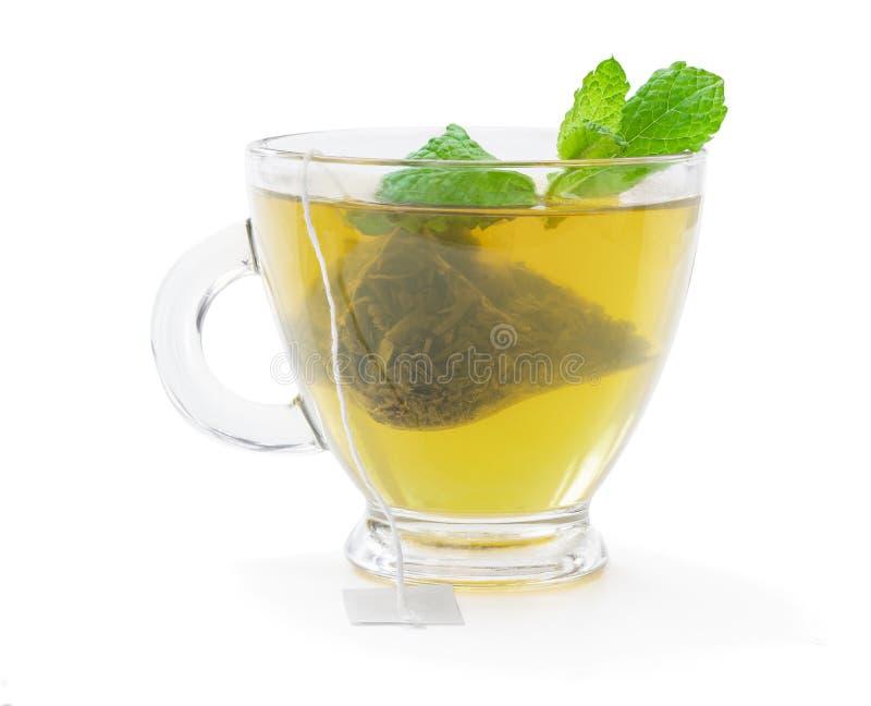 Cup of green tea with jasmine and pyramid tea bag isolated on white. Cup of  green tea with jasmine and pyramid tea bag isolated on white stock photos