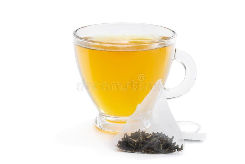 Cup of green tea with jasmine and pyramid tea bag isolated on white. Cup of  green tea with jasmine and pyramid tea bag isolated on white royalty free stock photo