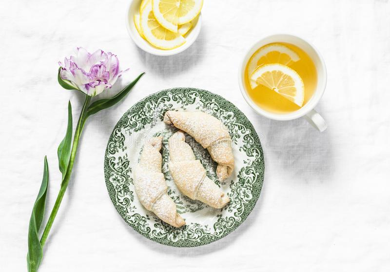 Cup of green tea with lemon, mini croissants, tulip flower - morning cozy still life on a white background, top view stock photos