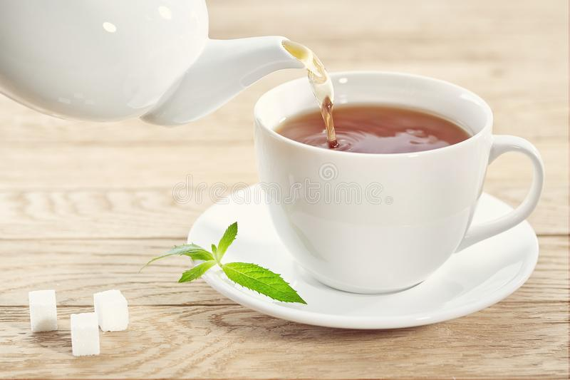 Cup with green tea, sugar and teapot on light wooden table background royalty free stock photo
