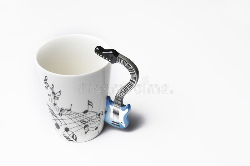 A cup with guitar handle. A cup for musician. Cup ispolated on white background.Copy space. A cup with guitar handle.  A cup for musician. Cup ispolated on white royalty free stock photography