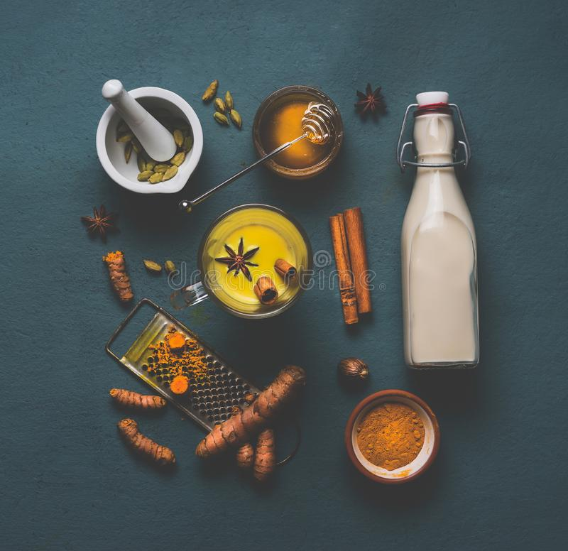 Cup of healthy golden turmeric spice milk with ingredients: cardamom, turmeric, cinnamon, honey and ginger royalty free stock photos