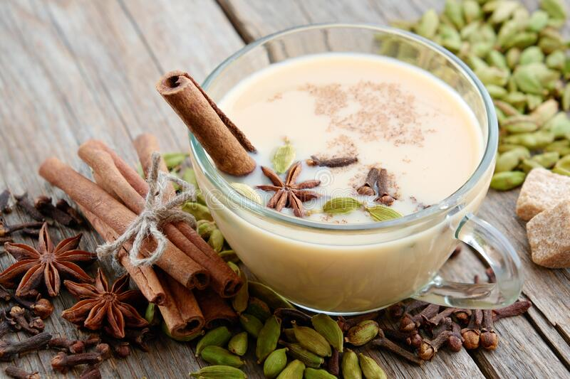 Cup of healthy masala tea with milk and aromatic spices and herbs. Ayurveda treatments. Cinnamon sticks, cardamom, allspices and anise on wooden table stock photo