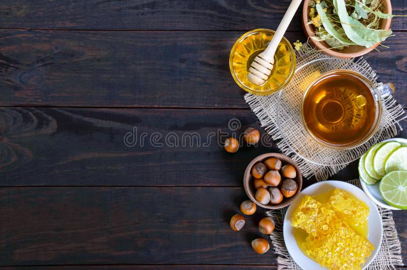 A cup of herbal tea, honey, honeycomb, hazelnuts on a dark wooden background. Healthy foods. Proper nutrition royalty free stock photos