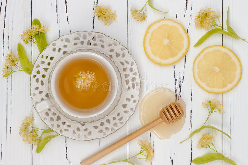 Cup of herbal tea with linden flowers, lemon and honey on a old wooden background. Top view stock photo