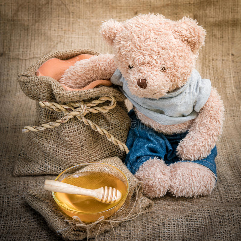 Cup honey on sackcloth. With Teddy Bear Vintage Style and selective focus royalty free stock photography