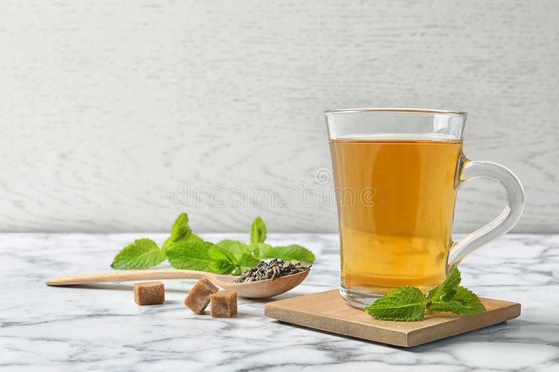 Cup of hot aromatic mint tea and spoon with dry leaves. On marble table stock image