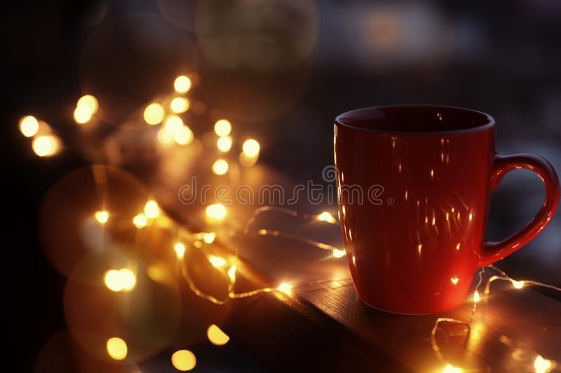 Cup of hot beverage on balcony railing decorated with Christmas lights, space for text royalty free stock image