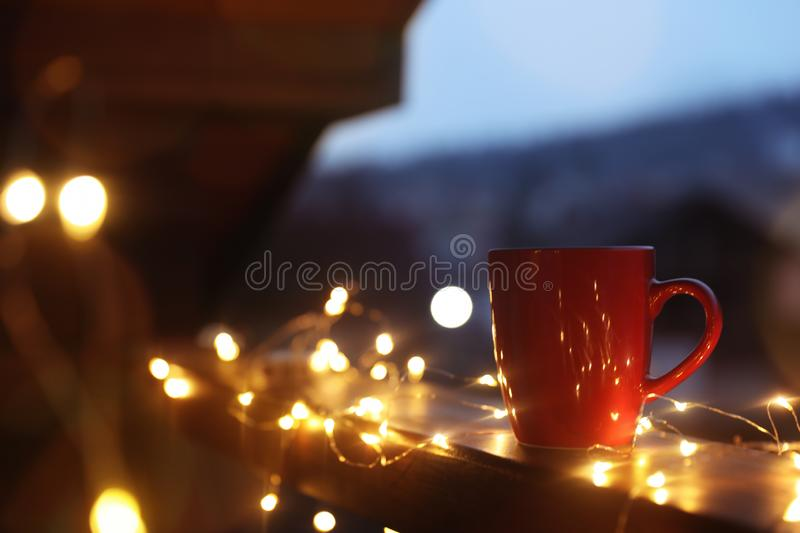Cup of hot beverage on balcony railing decorated with Christmas lights, space for text. Winter royalty free stock photos