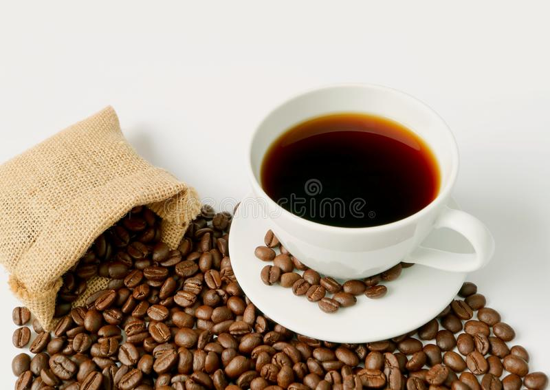 Cup of hot black coffee with heap of roasted coffee beans scattered from burlap sack royalty free stock photos