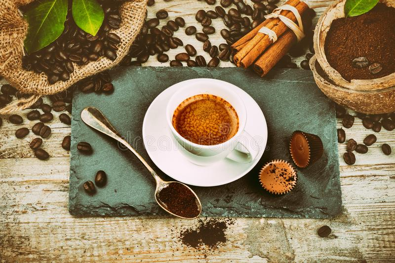 Cup of hot black coffee in setting with roasted coffee beans and stock photos