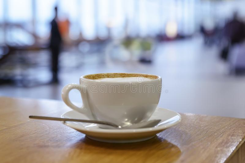 Cup of hot cappuccino coffee in a white cup is on the table in the airport lobby: royalty free stock image