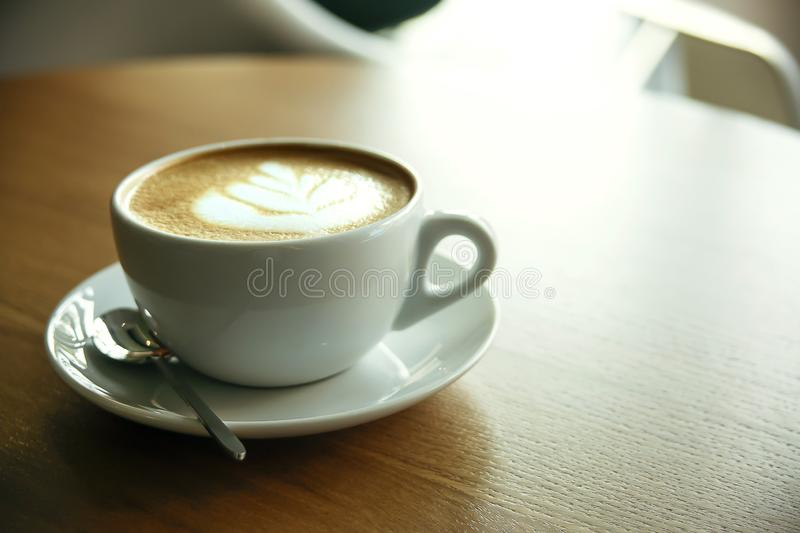 Cup of hot cappucino. On the wooden table. Early morning breakfast stock images