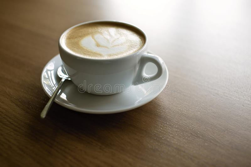 Cup of hot cappucino. On the wooden table. Early morning breakfast stock photos