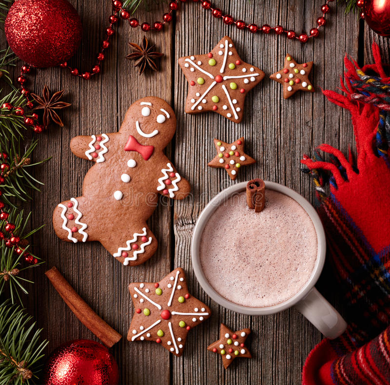 Cup of hot chocolate or cocoa with gingerbread man, warm scarf composition in fir tree decoration. Square view royalty free stock photos