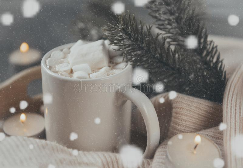 Cup hot chocolate cocoa with marshmallows, spruce branch, candles with lights, snowflakes, side view stock image