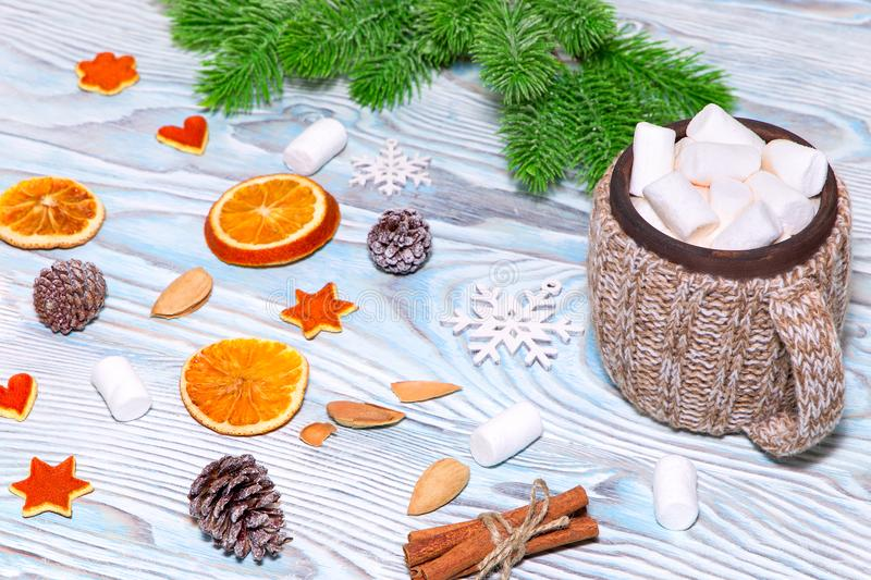 Cup of hot Chocolate drink with marshmallows, cinnamon sticks, dry oranges, cones and fir tree on light blue wooden background. stock photography