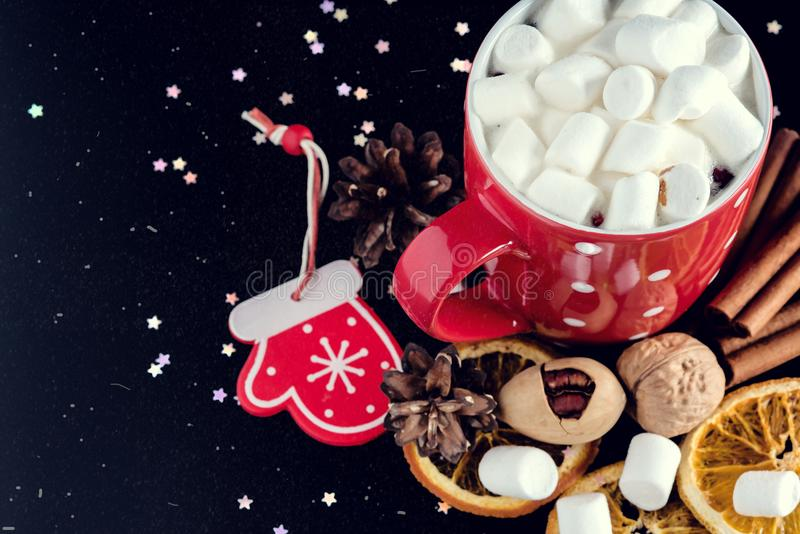 Cup of hot chocolate with marshmallow Nuts Cinnamon Orange on black background Above Copy space Toned with snow flakes stock images