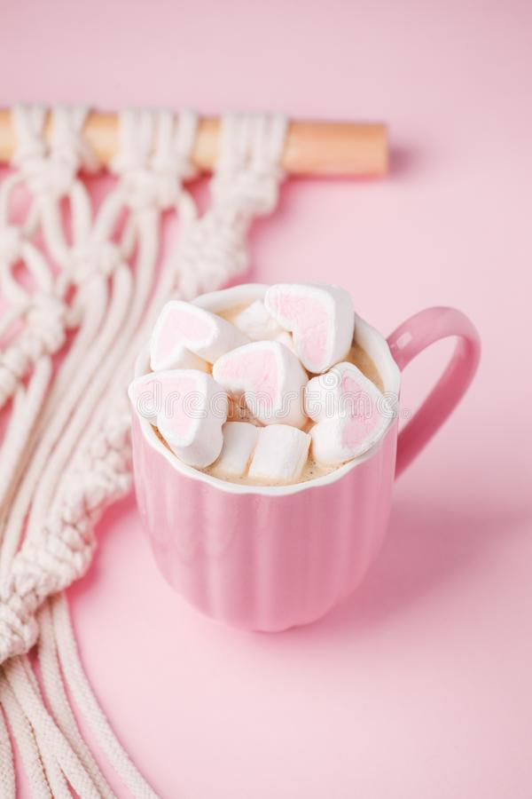 Cup of hot chocolate with pink heart shaped marshmallows and macrame panel on pink background, trendy minimal romantic composition stock photography