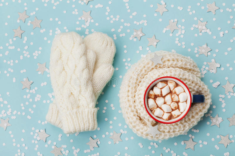 Cup of hot cocoa or chocolate with marshmallow and knitted mittens on blue winter background top view. Flat lay. stock photos