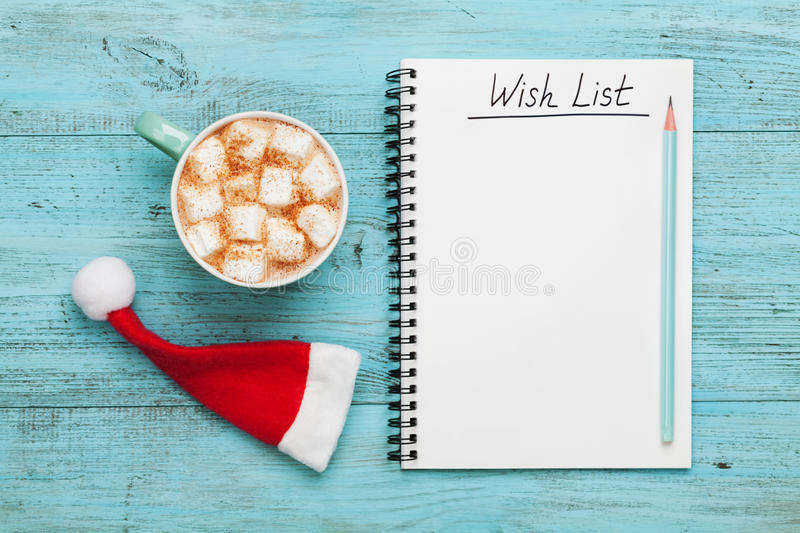 Cup of hot cocoa or chocolate with marshmallow, Santa Claus hat and notebook with wish list, christmas planning concept. Flat stock photo