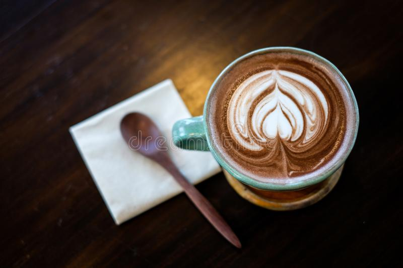 A cup of hot cocoa coffee or latte decorated with hearted milk royalty free stock image