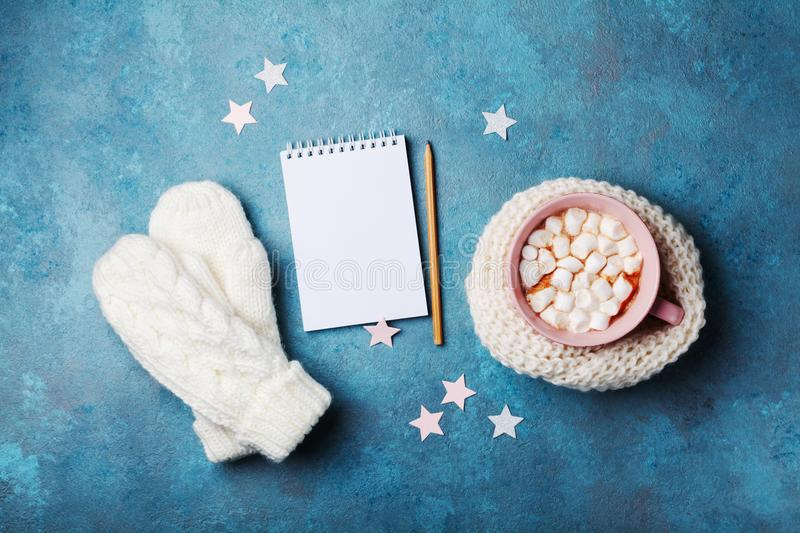 Cup of hot cocoa decorated knitted scarf with marshmallow, mittens and clean notebook on turquoise table top view. Flat lay style. Winter mockup royalty free stock photo